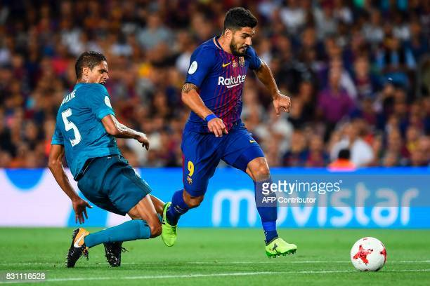 Real Madrid's French defender Raphael Varane vies with Barcelona's Uruguayan forward Luis Suarez during the first leg of the Spanish Supercup...