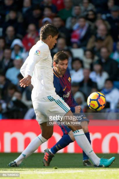 Real Madrid's French defender Raphael Varane vies with Barcelona's Argentinian forward Lionel Messi during the Spanish League 'Clasico' football...