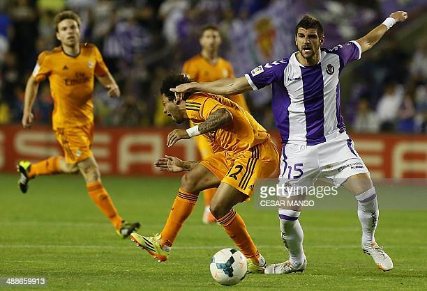 Real Madrid's French defender Raphael Varane vies with Valladolid's Serbian defender Stefan Mitrovic during the Spanish league football match Real...