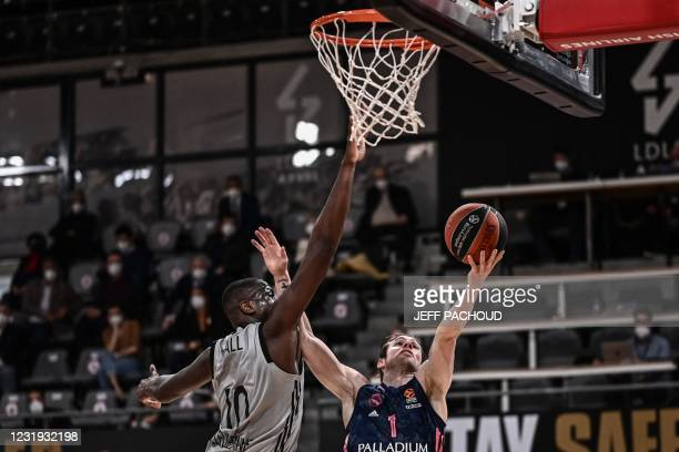 Real Madrid's French forward Fabien Causeur tries to score despite ASVEL's French centre Moustapha Fall during the Euroleague basketball match...