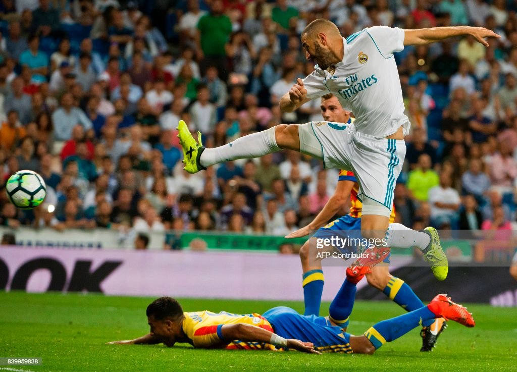 Real Madrid's French forward Karim Benzem (R) kicks the ball during the Spanish league football match Real Madrid CF vs Valencia CF at the Santiago Bernabeu stadium in Madrid on August 27, 2017. /