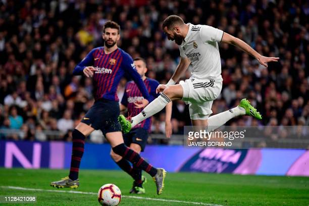 Real Madrid's French forward Karim Benzema advances with the ball past Barcelona's Spanish defender Gerard Pique during the Spanish league football...
