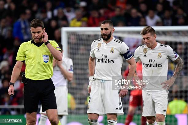 Real Madrid's French forward Karim Benzema and Real Madrid's German midfielder Toni Kroos wait next to German referee Felix Brych during the UEFA...