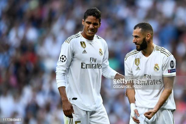 Real Madrid's French forward Karim Benzema ands Real Madrid's French defender Raphael Varane react during the UEFA Champions league Group A football...