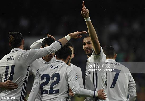 TOPSHOT Real Madrid's French forward Karim Benzema celebrates a goal with teammates during the Spanish league football match between Real Madrid CF...