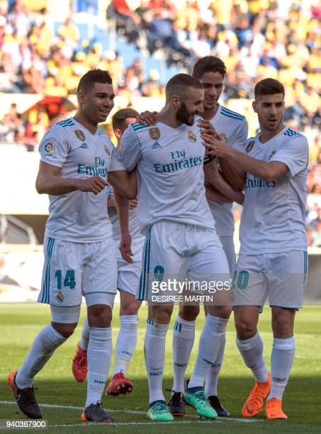 Real Madrid's French forward Karim Benzema celebrates a goal with teammates during the Spanish League football match between UD Las Palmas and Real...