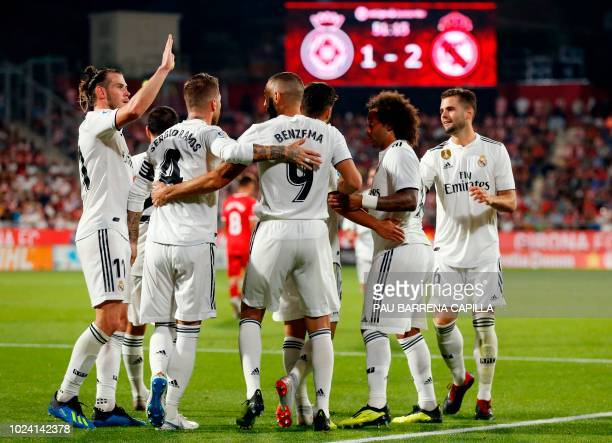 TOPSHOT Real Madrid's French forward Karim Benzema celebrates his goal with teammates during the Spanish league football match between Girona FC and...