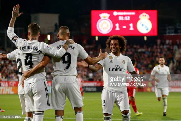 Real Madrid's French forward Karim Benzema celebrates scoring his team's second goal with teammates during the Spanish league football match between...