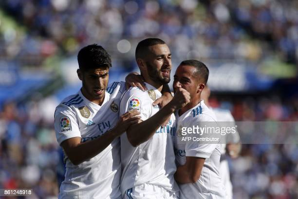 Real Madrid's French forward Karim Benzema celebrates with Real Madrid's Spanish midfielders Marco Asensio and Lucas Vazquez after scoring a goal...