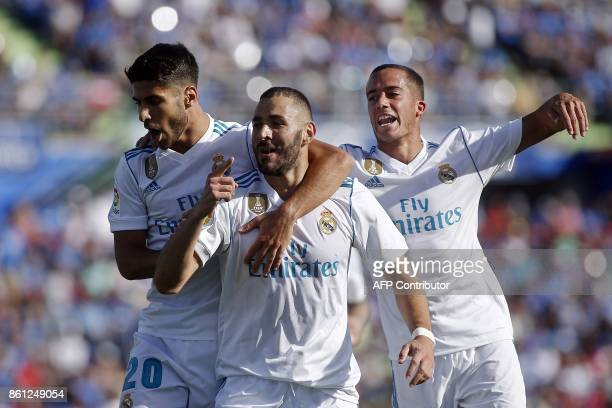 TOPSHOT Real Madrid's French forward Karim Benzema celebrates with Real Madrid's Spanish midfielders Marco Asensio and Lucas Vazquez after scoring a...