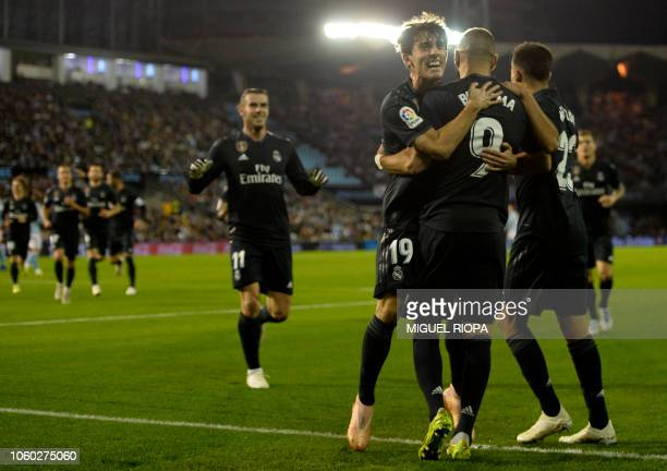 Real Madrid's French forward Karim Benzema celebrates with teammates after scoring the opening goal during the Spanish league football match between...