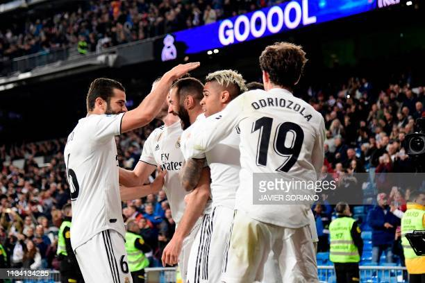 Real Madrid's French forward Karim Benzema celebrates with teammates after scoring his team's third goal during the Spanish League football match...