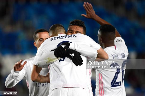 Real Madrid's French forward Karim Benzema celebrates with teammates after scoring his second goal during the UEFA Champions League group B football...