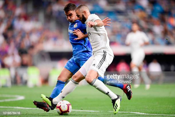 Real Madrid's French forward Karim Benzema challenges Getafe's Spanish defender Bruno Gonzalez during the Spanish League football match between Real...