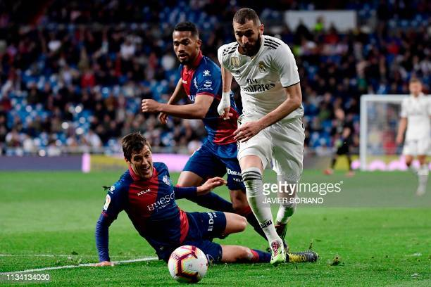 Real Madrid's French forward Karim Benzema challenges SD Huesca's Venezuelan midfielder Yangel Herrera and SD Huesca's Argentinian defender Martin...