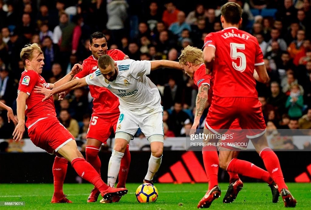TOPSHOT - Real Madrid's French forward Karim Benzema (C) challenges Sevilla's German midfielder Johannes Geis (L), Sevilla's Argentinian defender Gabriel Mercado (2ndL), Sevilla's Danish defender Simon Kjaer (2ndR) and Sevilla's French defender Clement Lenglet (R) during the Spanish league football match between Real Madrid and Sevilla at the Santiago Bernabeu Stadium in Madrid on December 9, 2017. /
