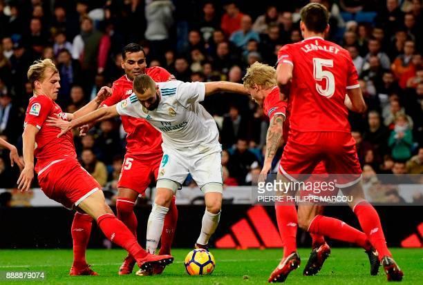 TOPSHOT Real Madrid's French forward Karim Benzema challenges Sevilla's German midfielder Johannes Geis Sevilla's Argentinian defender Gabriel...