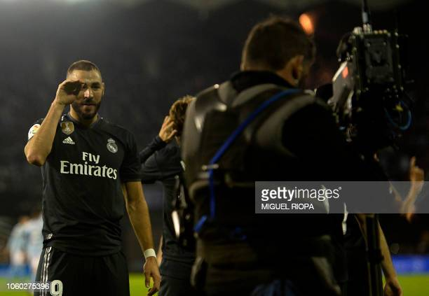 Real Madrid's French forward Karim Benzema gestures to a TV camera as he celebrates scoring the opening goal during the Spanish league football match...