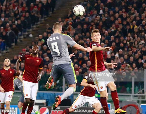 Real Madrid's French forward Karim Benzema heads the ball against Roma's defender from France Lucas Digne during the UEFA Champions League round of...