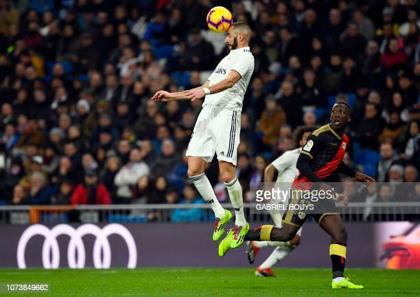 Real Madrid's French forward Karim Benzema heads the ball beside Rayo Vallecano's Peruvian defender Luis Advincula during the Spanish League football...