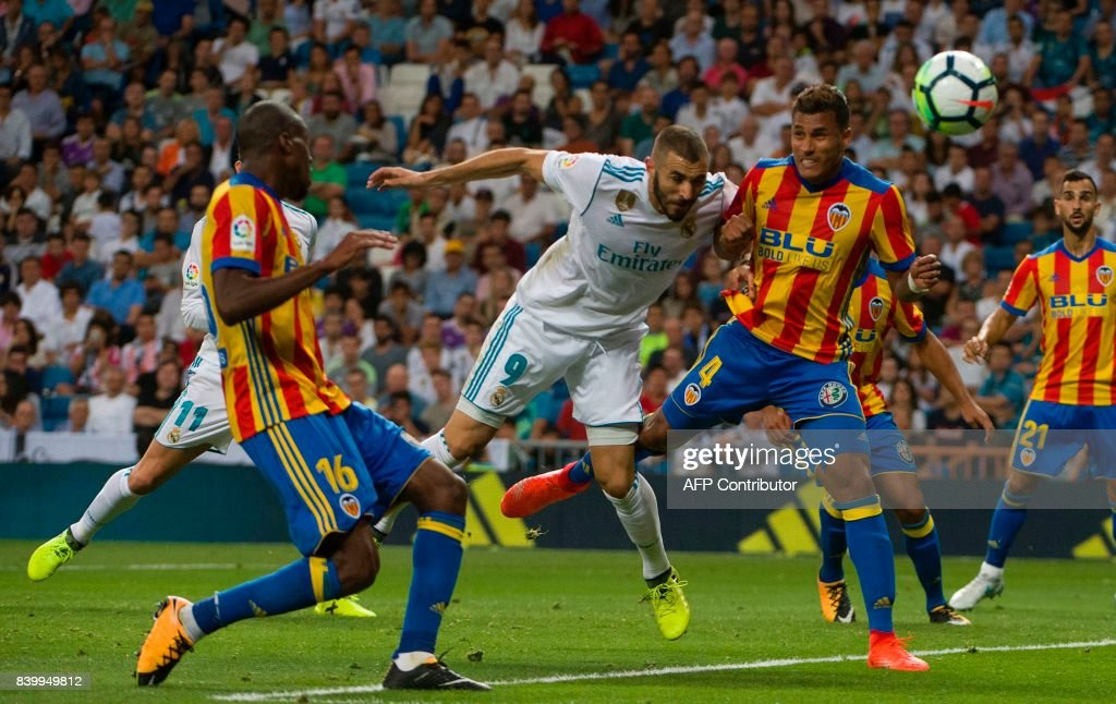 TOPSHOT - Real Madrid's French forward Karim Benzema (C) heads the ball past Valencia's Brazilian defender Jeison Murillo (R) during the Spanish league football match Real Madrid CF vs Valencia CF at the Santiago Bernabeu stadium in Madrid on August 27, 2017. /