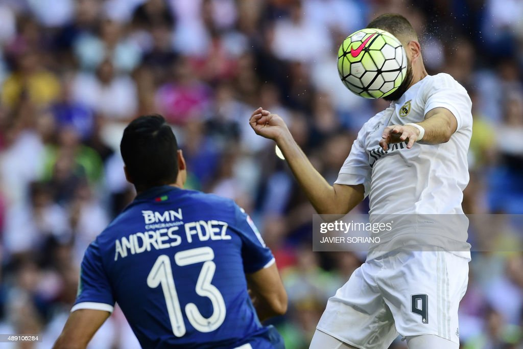 Real Madrid's French forward Karim Benzema (R) heads the ball to score during the Spanish league football match Real Madrid CF vs Granada FC at the Santiago Bernabeu stadium in Madrid on September 19, 2015.