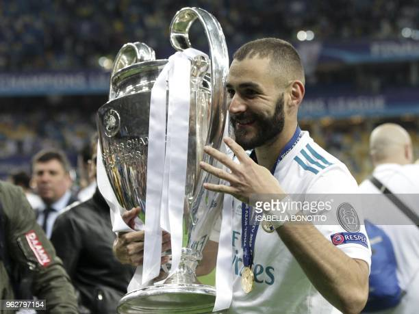 Real Madrid's French forward Karim Benzema holds the trophy after winning the UEFA Champions League final football match between Liverpool and Real...
