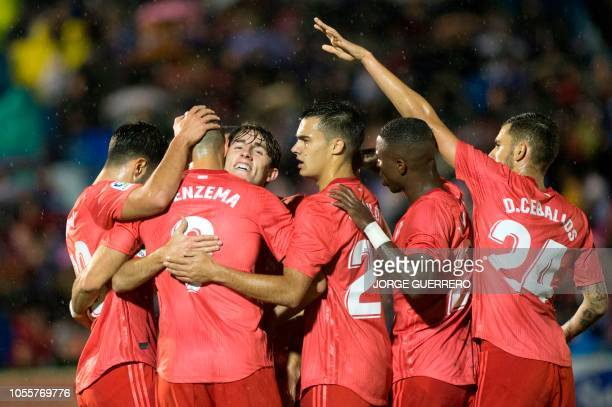 Real Madrid's French forward Karim Benzema is congratulated by teammates after scoring a goal during the Spanish King's Cup football match between UD...