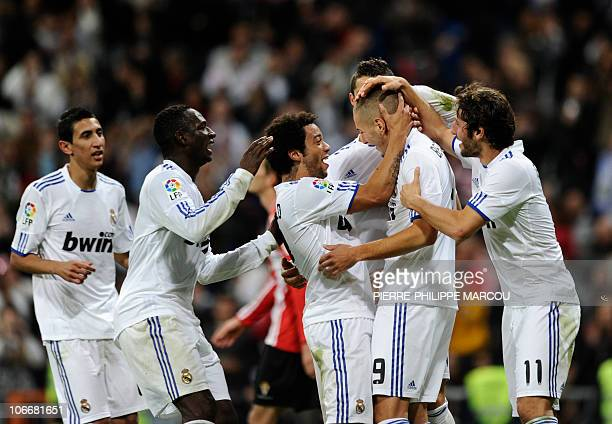 Real Madrid's French forward Karim Benzema is congratulated by teammates Argentinian midfielder Angel di Maria Malian midfielder Mahamadou Diarra...