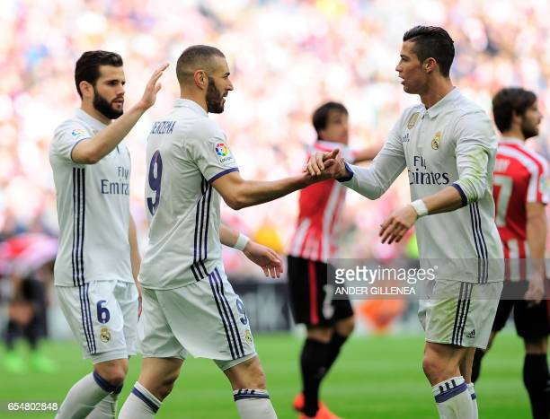 Real Madrid's French forward Karim Benzema is congratulated by teammates Portuguese forward Cristiano Ronaldo and defender Nacho Fernandez after...