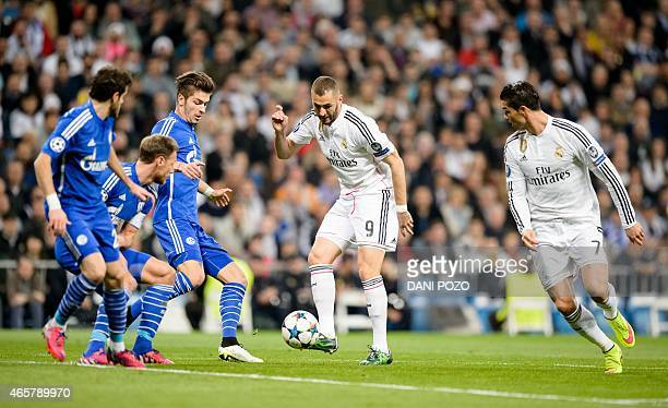 Real Madrid's French forward Karim Benzema pass the ball to Real Madrid's Portuguese forward Cristiano Ronaldo during the round of 16 second leg UEFA...