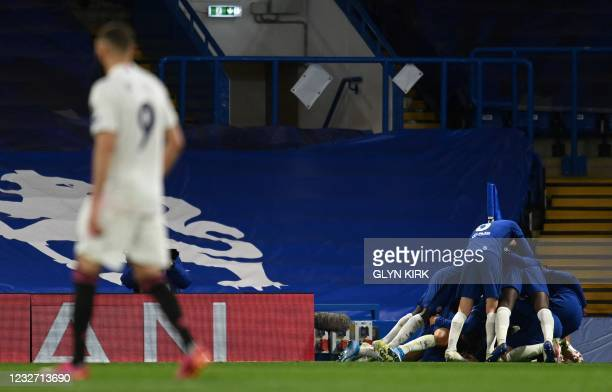 Real Madrid's French forward Karim Benzema reacts as Chelsea's English midfielder Mason Mount is mobbed by teammates after scoring the second goal...