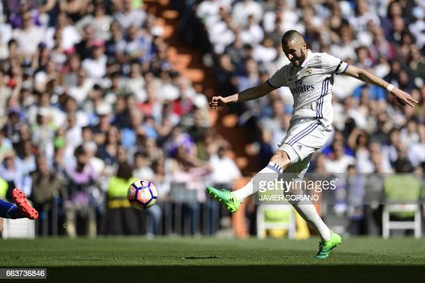Real Madrid's French forward Karim Benzema shoots to score a goal during the Spanish league football match Real Madrid CF vs Deportivo Alaves at the...