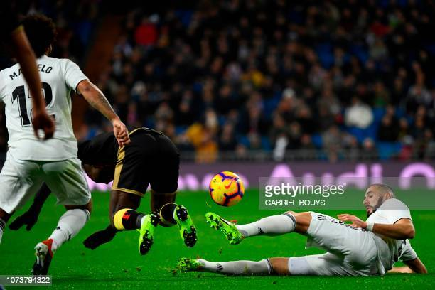Real Madrid's French forward Karim Benzema tackles Rayo Vallecano's Peruvian defender Luis Advincula during the Spanish League football match between...
