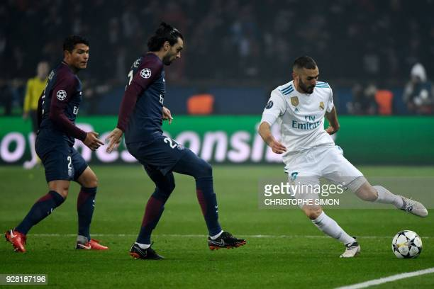 Real Madrid's French forward Karim Benzema vies for the ball with Paris SaintGermain's Argentinian midfielder Javier Pastore and Paris SaintGermain's...