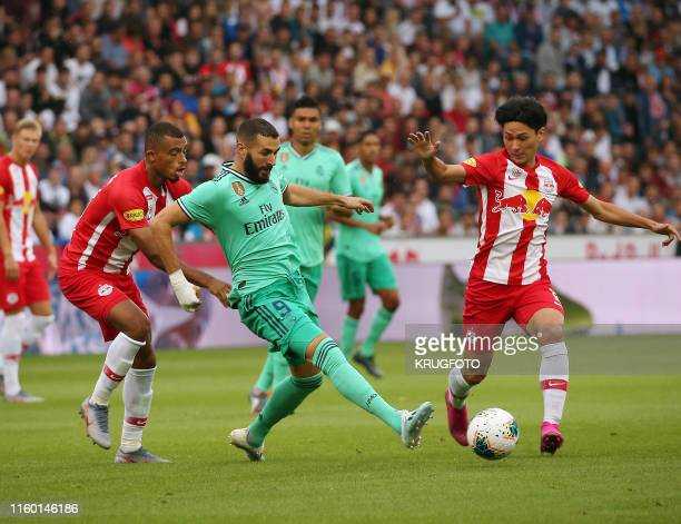Real Madrid's French forward Karim Benzema vies for the ball with Red Bull Salzburg's French midfielder Antoine Bernede and Red Bull Salzburg's...