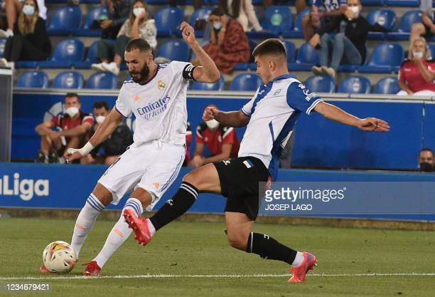 Real Madrid's French forward Karim Benzema vies with Alaves' Spanish midfielder Pere Pons during the Spanish League football match between Alaves and...