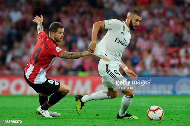 Real Madrid's French forward Karim Benzema vies with Athletic Bilbao's Spanish defender Inigo Martinez during the Spanish league football match...