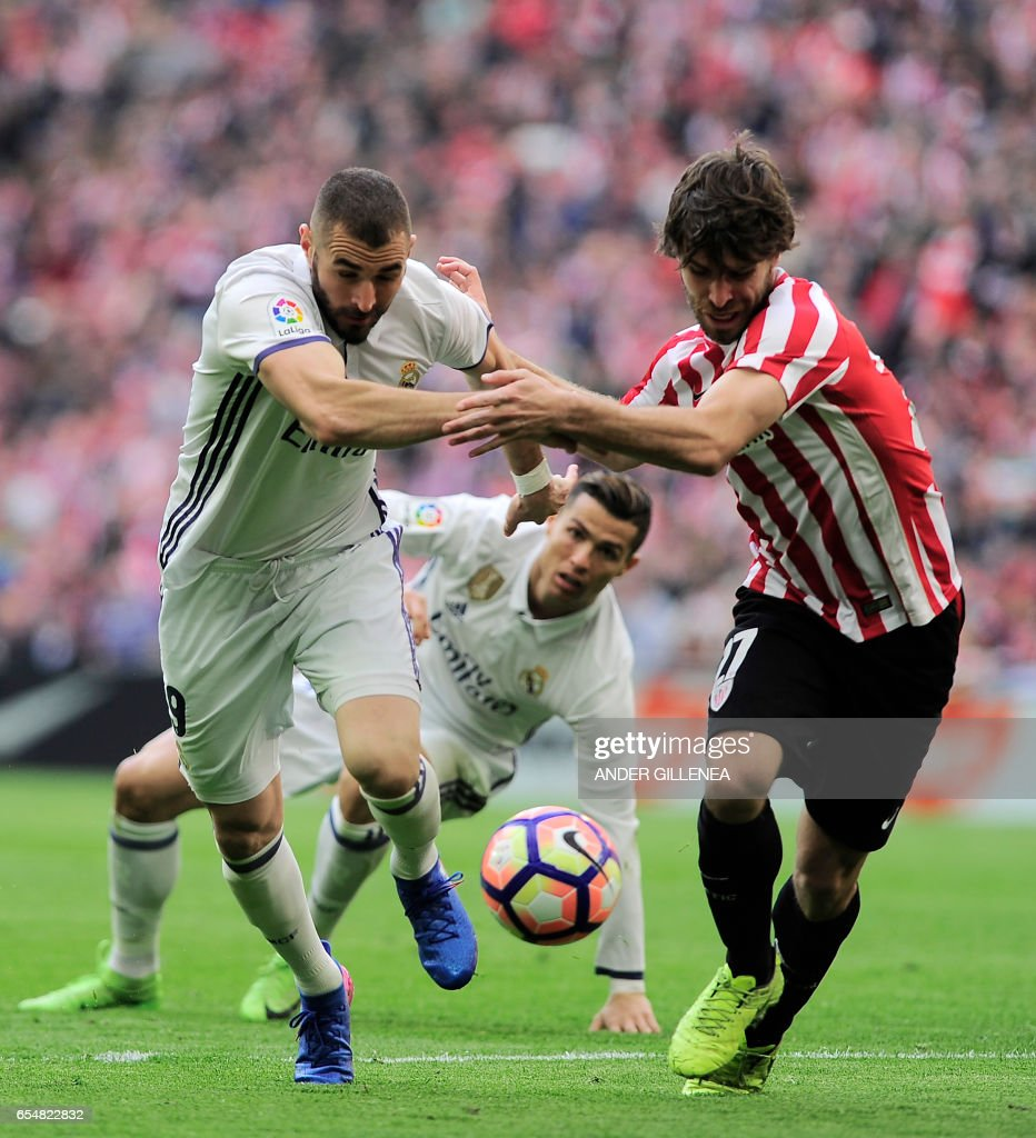 Real Madrid's French forward Karim Benzema (L) vies with Athletic Bilbao's defender Yeray Alvarez (R) during the Spanish league football match Athletic Club Bilbao vs Real Madrid CF at the San Mames stadium in Bilbao on March 18, 2017. /