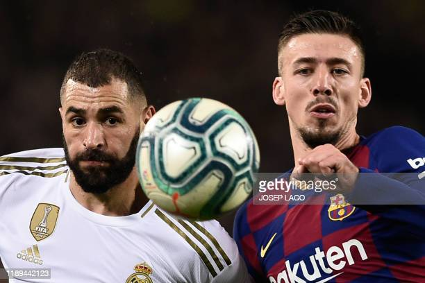 Real Madrid's French forward Karim Benzema vies with Barcelona's French defender Clement Lenglet during the El Clasico Spanish League football match...