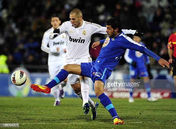 Real Madrid's French forward Karim Benzema vies with Getafe's defender Miguel Torres during their Spanish league football match Getafe against Real...