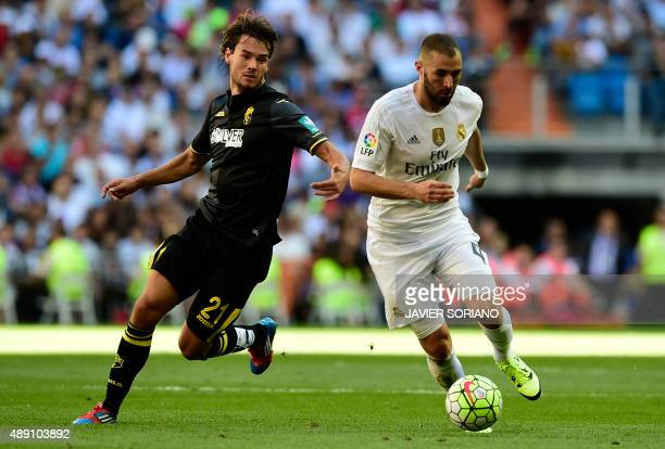 Real Madrid's French forward Karim Benzema vies with Granada's Slovenian midfielder Rene Krhin during the Spanish league football match Real Madrid...