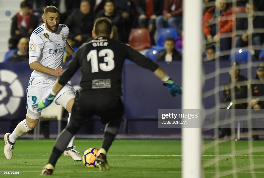 Real Madrid's French forward Karim Benzema (L) vies with Levante's goalkeeper Oier Olazabal during the Spanish league football match between Levante UD and Real Madrid CF at the Ciutat de Valencia stadium in Valencia on February 03, 2018. /
