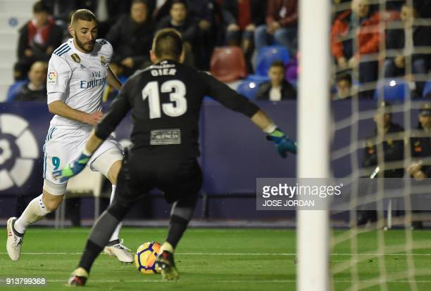 Real Madrid's French forward Karim Benzema vies with Levante's goalkeeper Oier Olazabal during the Spanish league football match between Levante UD...