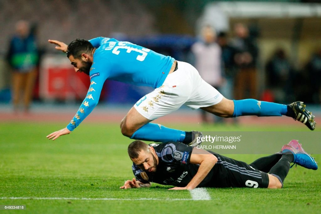 TOPSHOT - Real Madrid's French forward Karim Benzema (bottom) vies with Napoli's defender from Spain Raul Albiol during the UEFA Champions League football match SSC Napoli vs Real Madrid on March 7, 2017 at the San Paolo stadium in Naples. Real Madrid won 1-3. / AFP PHOTO / Carlo Hermann