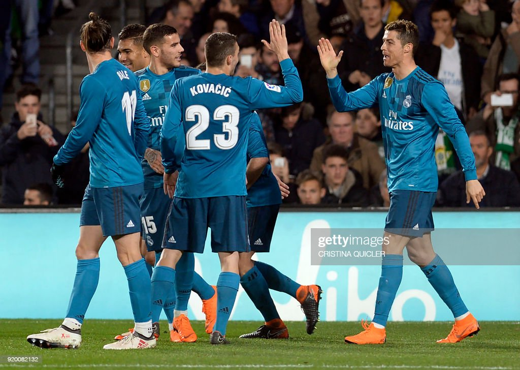 TOPSHOT - Real Madrid's French forward Real Madrid's Portuguese forward Cristiano Ronaldo (R) celebrates scoring a goal with teammates during the Spanish league football match Real Betis vs Real Madrid at the Benito Villamarin stadium in Sevilla on February 18, 2018. / AFP PHOTO / Cristina Quicler