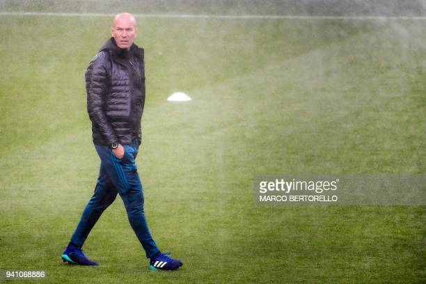 Real Madrid's French head coach Zinedine Zidane walks on the pitch as sprinklers spray water during a team training session on the eve of the UEFA...