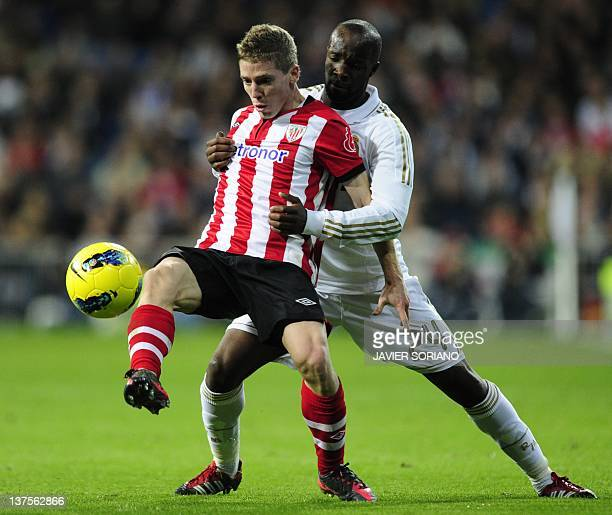 Real Madrid's French midfielder Lassana Diarra vies with Athletic Bilbao's forward Iker Muniain during the Spanish league football match Real Madrid...
