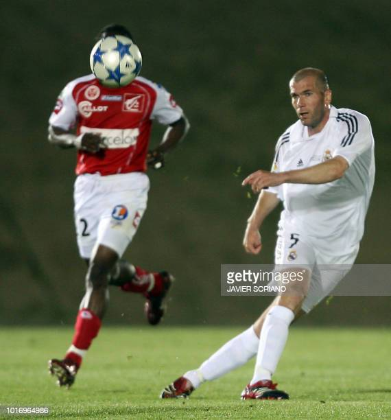 Real Madrid's French Zinedine Zidane gives a pass in front of Stade Reims' Nzigou during a friendly football match at the new Alfredo Di Stefano...