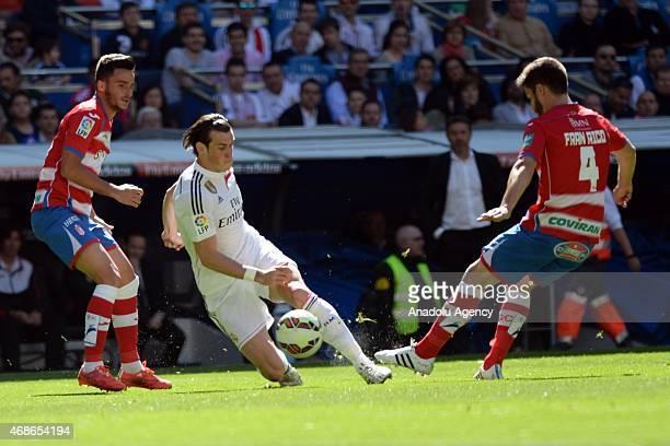 Real Madrid's Gareth Bale vies with Granada's Fran Rico during the Spanish La Liga football match between Real Madrid CF vs Granada CF at the...